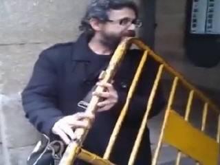 Уличный музыкант играет на заборе
